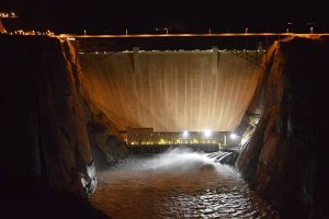 A large dam at night, lit by floodlights