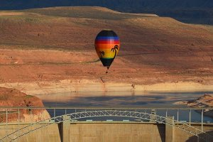 A hot air balloon rising in front of a dam and bridge