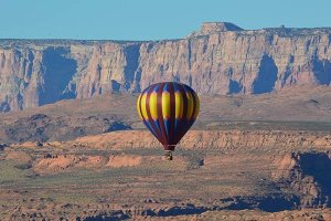 A blue and gold hot air balloon rising near red sandstone cliffs