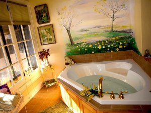 A room with a jetted tub and nature scenes on the walls