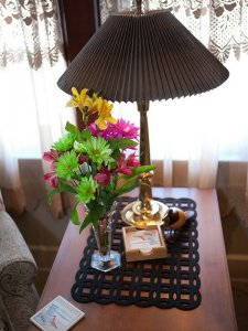 A lamp and bouquet of green, pink, and yellow flowers