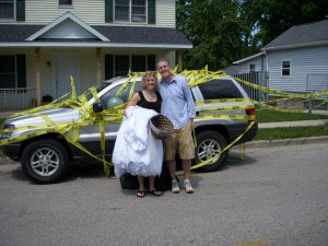 A bride and groom with a decorated car