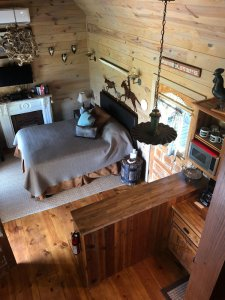 front room and bed looking down from the loft