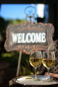 Two glasses of wine near a welcome sign