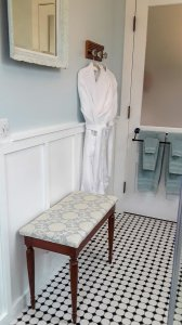 Cozy robes hanging next to bench in bathroom
