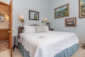 king size bed with impressionist artwork on walls
