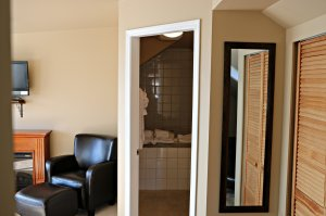 View of the entrance to the washroom, mirror and storage space