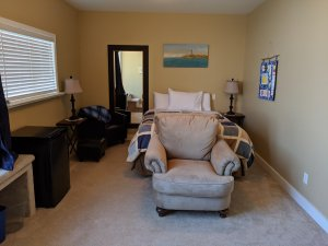 Overview of room showing bed, armchair, fridge, additional seat, mirror and bedside tables with lamps