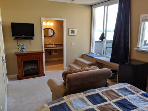 View of room from the back wall, showing arm chair, fireplace, tv, washroom door and balcony