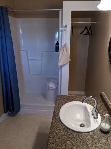 Washroom showing sink, space to hang clothes and stand alone shower with built in seat