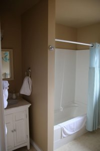 Image of washroom showing bath tub with shower and sink area