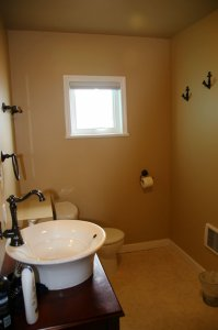 Another view of washroom showing large sink, toilet and window
