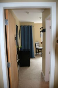 View from the entrance to the room showing fridge and storage behind curtain
