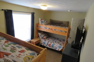 A room with two bunk beds and open curtains