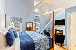 Room with blue bedding and fireplace