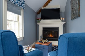 two blue chairs with TV over fireplace
