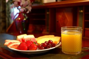 platter of fruit and a glass of orange juice