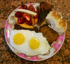 breakfast with eggs, fruit, meat and rolls