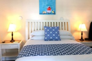 bed with blue pillow and blanket painting of bird above headboard