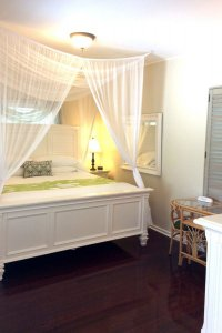 canopied bed with green highlights next to small table