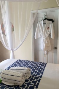 bed with canopy and rolled towels and robe