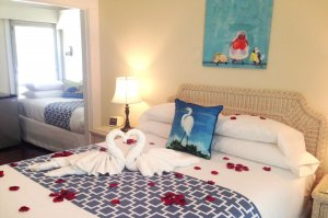 bed with rose petals and towel swans