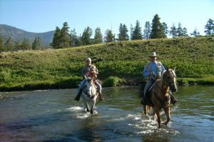 Two horses and riders going through a stream