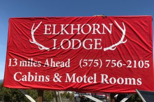 Elkhorn Lodge billboard 13 miles ahead 575-756-2105 Cabins and Motel rooms
