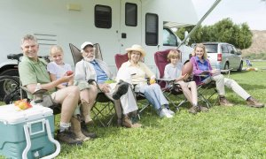 A family seated in front of an RV