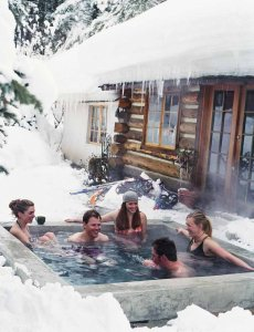 A group in a hot tub surrounded by snow