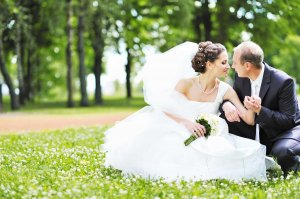 A couple in wedding clothes sits on grass