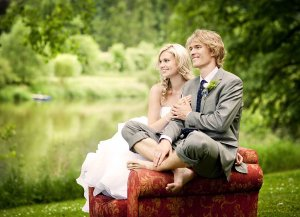 A couple in wedding clothes sites on a sofa outdoors