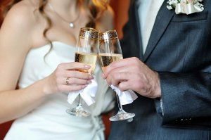 A couple in wedding clothes with champagne glasses