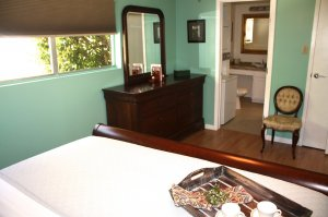 bed with tea tray and green walls