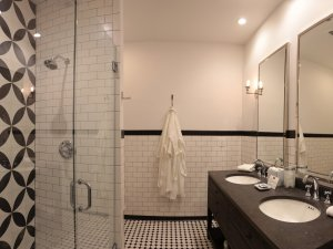 Bathroom with two sinks, walk in shower, and bath robe