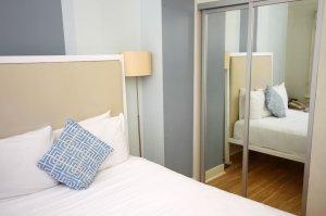 bed beside mirror closet