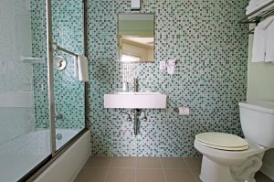 tub and toilet with turquoise tile wall