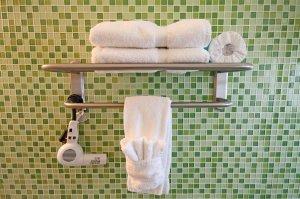 green tile wall and towel rack