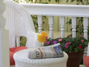 mimosa and newspaper with wicker furniture on front porch