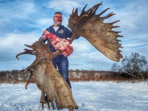 Hunter with moose shull and antlers