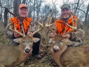 Two hunters with their harvested white tails