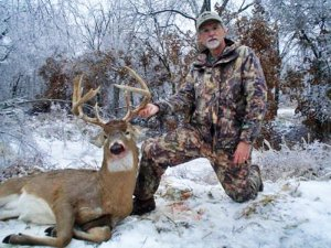 Hunter with harvested Deer in Snow