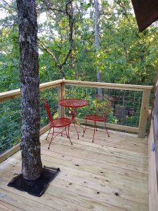 cafe table with two chairs on treehouse porch