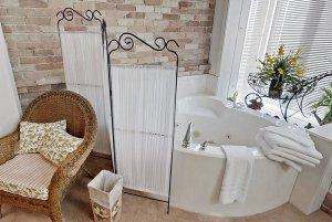 wicker chair near dressing curtain and bathtub