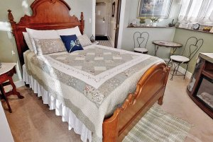 wooden bed with quilt and pillows
