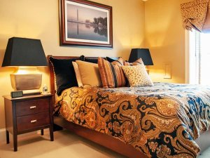 Bed next to bedside tables with lamps