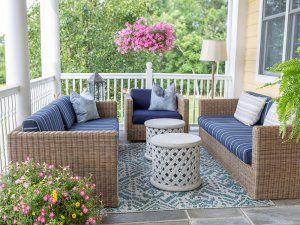 Comfortable furniture on porch next to flowers