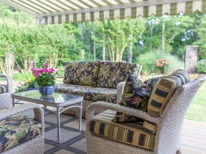 Cushioned wicker furniture under awning on deck