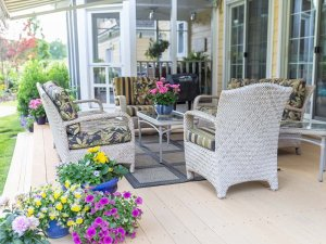 Flowers around furniture on wood deck