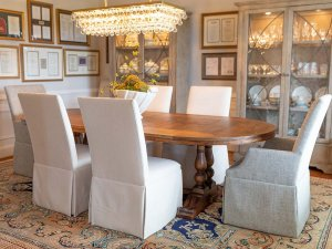 Covered chairs around table in dining room